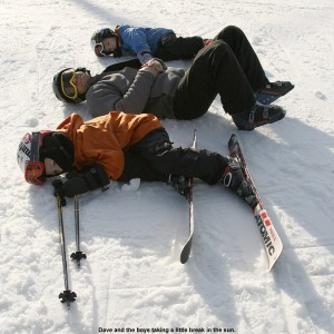 An image of Dave and the boys laying on the snow