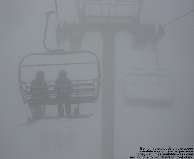 An image of snowboarders riding the Vista Quad Chair in heavy fog at Bolton Valley Ski Resort in Vermont