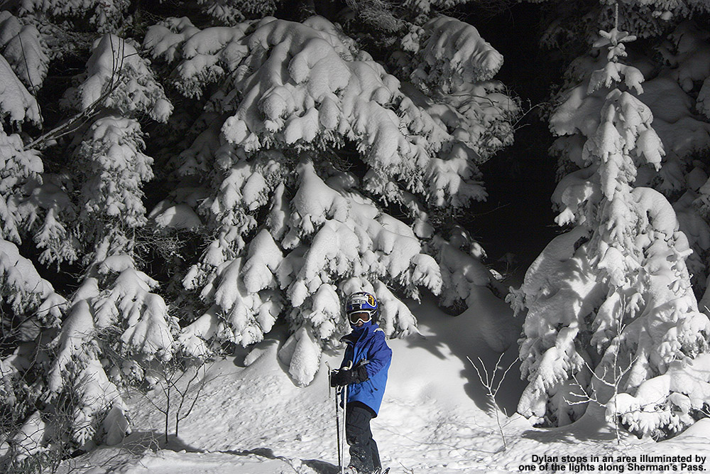 An iamge of Dylan in front of snow-covered evergreens lit up by the night skiing lights at Bolton Valley Resort in Vermont