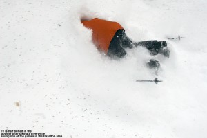 An image of Ty half buried in powder in one of the gullies in the Hazelton Zone at Stowe Mountain Ski Resort in Vermont