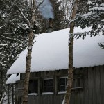 An image of the Bryant Cabin with smoke coming from the chimney on the Nordic/backcountry trail network at Bolton Valley Ski Resort in Vermont