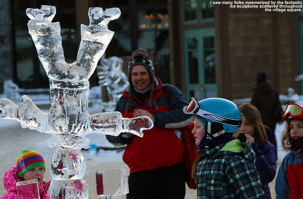 An image of an ice sculpture and onlookers  in the middle of the Spruce Peak Village at Stowe Ski Resort in Vermont