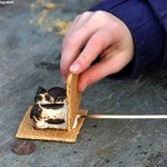 An image of a s'more being assembled at the fire pit in the center of the Spruce Peak Village at Stowe Mountain Ski Resort in Vermont