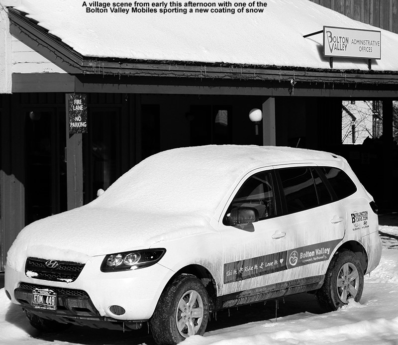 An image of one of the Bolton Valley resort vehicles in the village circle with a coating of snow