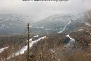 An image of Mt. Mansfield capped with clouds and the ski trails near the Gondola at Stowe Mountain Resort in Vermont