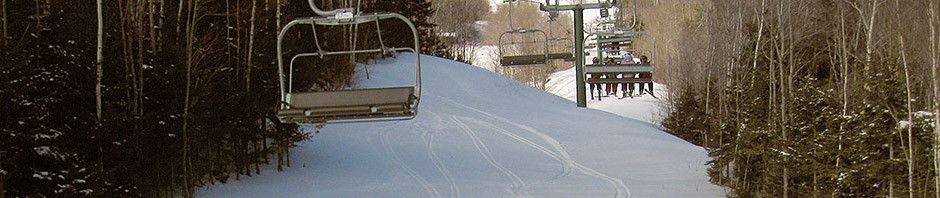 An image of ski tracks in the powder underneath the Sensation High Speed Quad Chairlift at Stowe Mountain Resort in Vermont