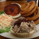 An image of the pulled pork sanwich along with coleslaw and onion rings at the James Moore Taver at Bolton Valley Ski Resort in Vermont