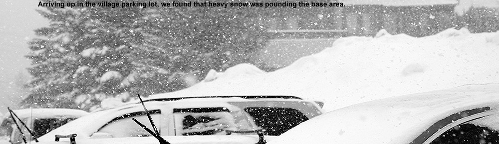 An image of cars parked in the Bolton Valley Village under heavy snowfall at Bolton Valley Ski Resort in Vermont