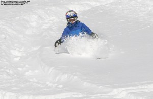 An image of Dylan skiing some deep powder in the sunshine above the Meadows Trail at Stowe Mountain Resort in Vermont
