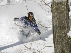 An image of Jay skiing deep powder in the Ridge Run trees on Spruce Peak at Stowe Mountain Resort in Vermont