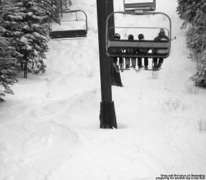 An image of Greg and some of the boys in our ski group on the Sensation Quad at Stowe Mountain Resort, with tracks visible in the powder on the lift line trail below