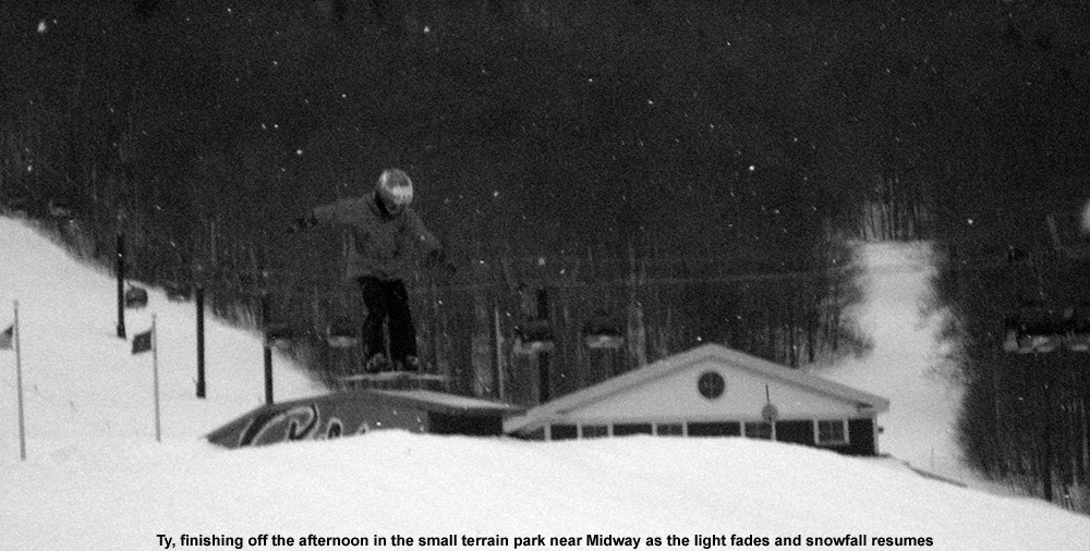 An image of Ty jumping over a sloped box in the small terrain park near the Midway Lodge at Stowe Mountain Ski Resort in Vermont