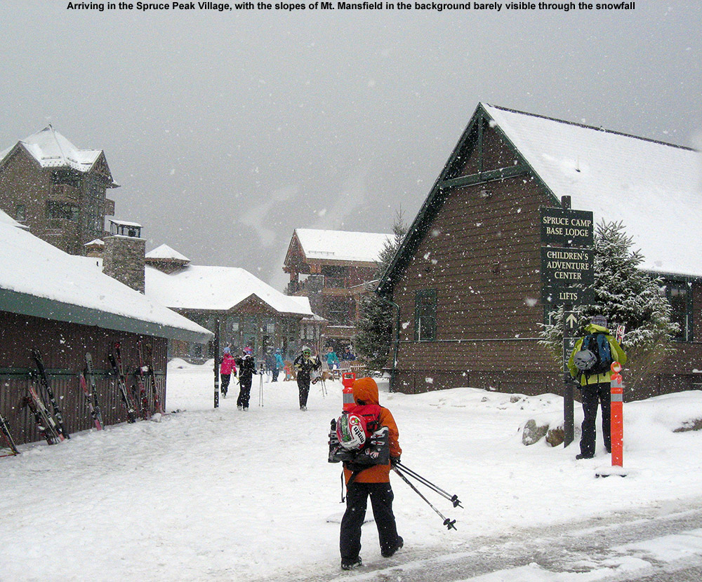 An image of arriving at the Spruce Peak Village at Stowe Ski Resort in Vermont with snow falling and a couple of trails on Mt. Mansfield just visible in the background