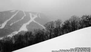 An image taken from the Sunny Spruce Quad on Spruce Peak at Stowe Mountain Ski Resort in Vermont, showing some of the trails on Mount Mansfield, with the gondola area under The Chin hidden by snowfall