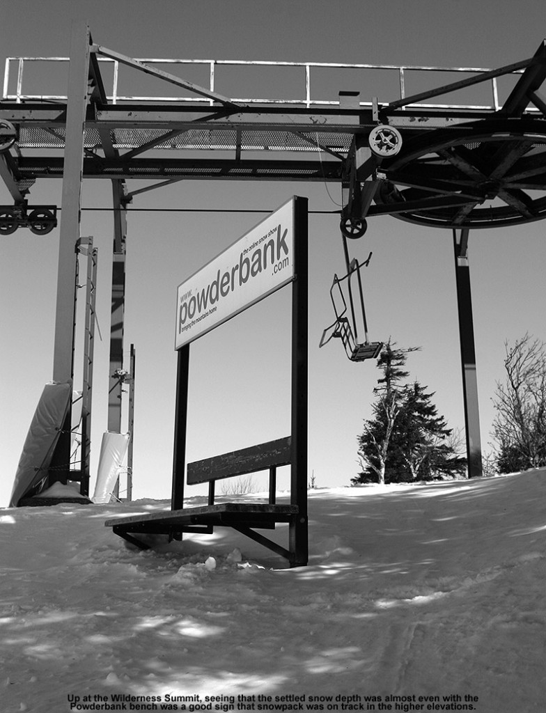 An image of the bench with the Powderbank sign at the summit of the Wilderness area at Bolton Valley Ski Resort in Vermont - the snowpack is several feet deep and is just about level with the seat of the bench.