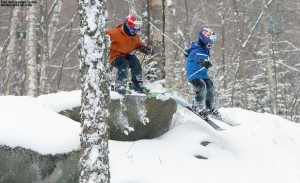 An image of Ty and Dylan jump off a rock into the powder in the Wilderness Woods at Bolton Valley Ski Resort in Vermont