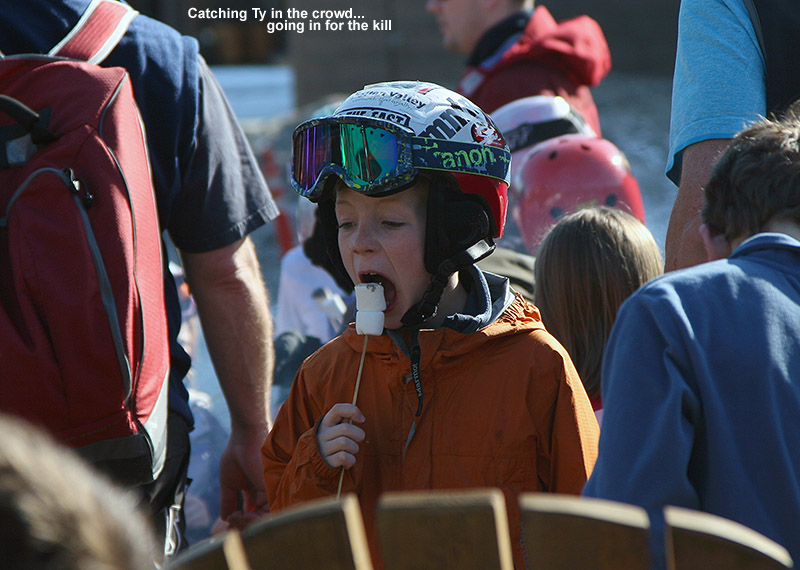 An image of Ty eating toasted marshmallows on a stick among the crowd at the Spruce Peak Village fire pit at Stowe Mountain Ski Resort in Vermont