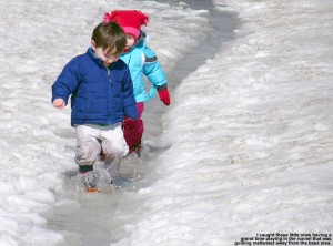 An image of a couple of young children playing in the water in a spring drainage runnel at the base of Bolton Valley Ski Area in Vermont