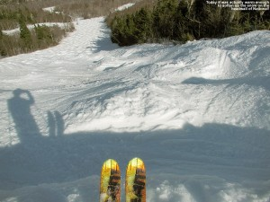An image of skis poking out over the steep edge of the headwall of the National trail at Stowe Mountain Resort in Vermont, with the steep, snowy, mogul-filled trail below