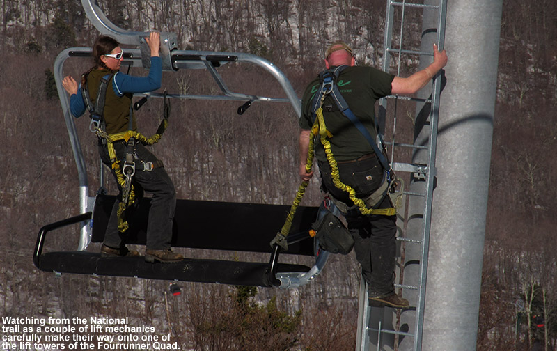 An image of two lift mechanics with safety harnesses moving from a chair on Stowe's Fourrunner Quad to one of the towers to perform maintenance.