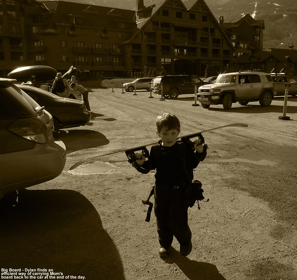 An image of Dylan carrying Erica's snowboard on his shoulders as he walks through the parking lot in front of the Stowe Mountain Lodge at Stowe Mountain Ski Resort in Vermont