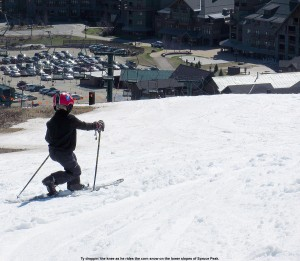 An image of Ty Telemark skiing in spring snow on the lower slopes of Spruce Peak at Stowe Mountain Resort in Vermont