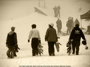 An image of four snowboarders walking up for another run in the terrain park at Stowe - March 25, 2012