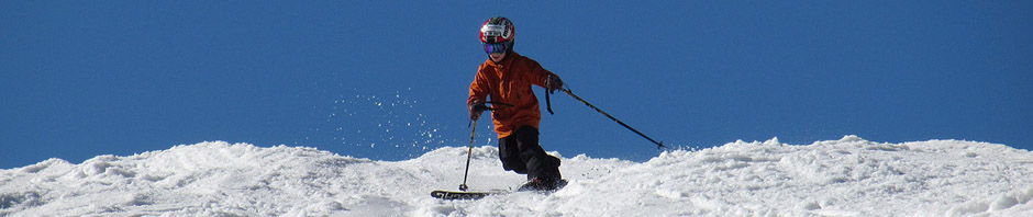 An image of Ty Telemark skiing in spring snow on the Ridge View Trail at Stowe Mountain Resort in Vermont
