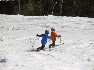 An image of Ty and Dylan Telemark skiing together in spring snow on the Ridge View trail at Stowe Mountain Resort in Vermont