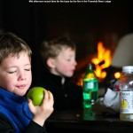 An image of Ty and Dylan having a mid afternoon snack near the fire in the Tramside Base Lodge at Jay Peak Ski Resort in Vermont