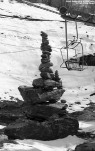 A pile of balanced rocks sits at the base of the Vista Quad Chairlift at Bolton Valley Ski Resort in Vermont, with snow from a recent April storm in the background