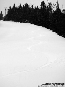 An image of ski tracks in late April powder on the Sunrise trail at Stowe Mountain Resort in Vermont