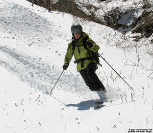 An image of E skiing some powder off the edge of North Slope at Stowe Mountain Resort in Vermont after an April snowstorm
