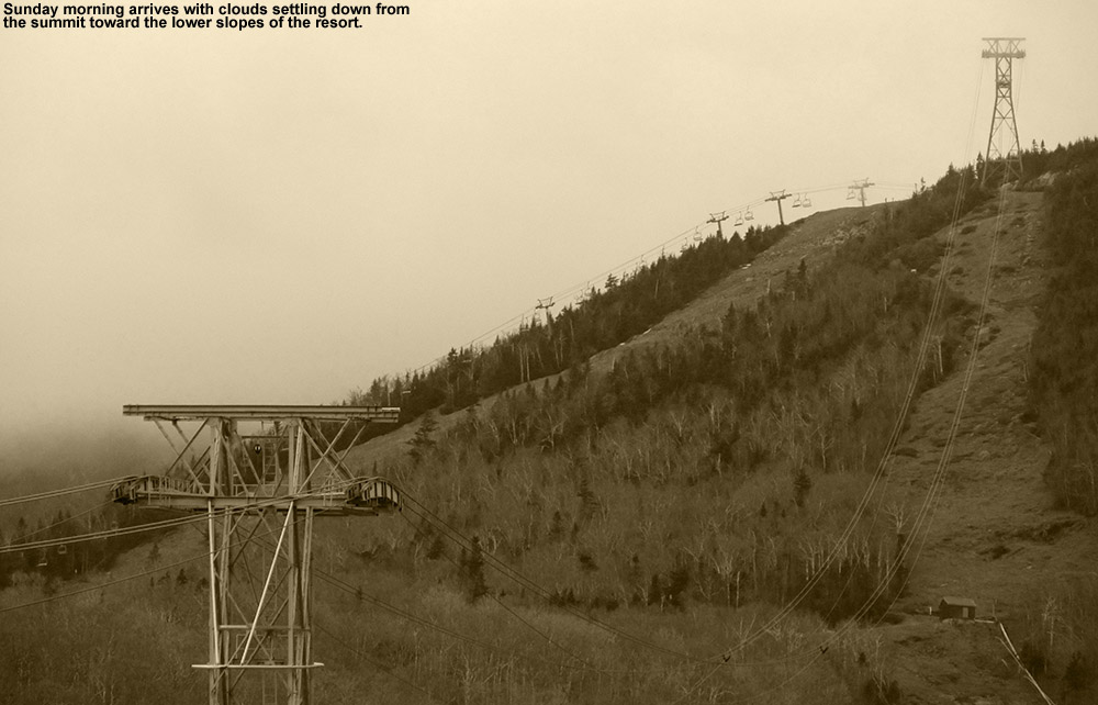An image of tram and chairlift towers under descending clouds from the tram base area at Jay Peak Ski Resort in Vermont