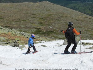 An image of Jay advising Dylan as he skies though a narrow area with rocks on the Mount Washington east snowfields - Memorial Day Weekend 2012