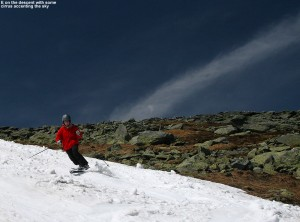 An image of Erica skiing the snowfields on Mount Washington in New Hampshire, with a stripe of cirrus clouds among blue sky in the background