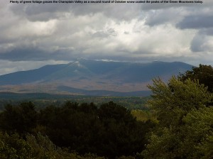 An image showing Vermont's second October snowfall coating the summit of Mt. Mansfield, with green trees in the Champlain Valley marking the foreground