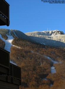 An image of balconies of the Stowe Mountain Lodge at Stowe Mountain Ski Resort in Vermont, with the Nose area of Mt. Mansfield in the background under blue skies