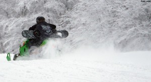 An image of skiers using a snowmobile to ski laps on terrain at Bolton Valley Ski Resort in Vermont
