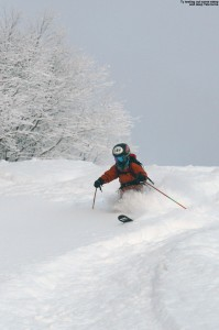 An image of Ty Telemark skiing in powder on the headwall of the Showtime trail at Bolton Valley Ski Resort in Vermont