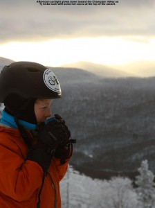 An image of Ty drinking hot cocoa at the Timberline Mid Station at Bolton Valley Ski Resort in Vermont, with late day light peeking through the clouds in the background