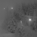 An image of snow covered trees and night skiing lights on the upper mountain in mid afternoon due to low clouds and December darkness at Bolton Valley Ski Resort in Vermont