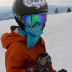 An image of Ty with a handkerchief mask outside the Octagon at the top of the Fourrunner Quad at Stowe Mountain Ski Resort in Vermont