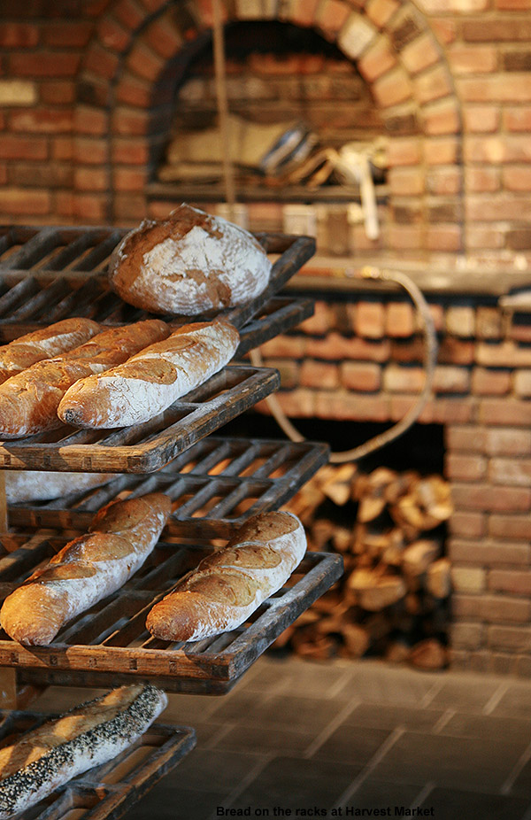 An image of bread on racks with firewood and bricks in the background at Harvest Market in Stowe, Vermont