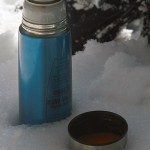 An image of a thermos and cup sitting in powder snow outside the Bryant Lodge on the backcountry trail network at Bolton Valley Ski Resort in Vermont