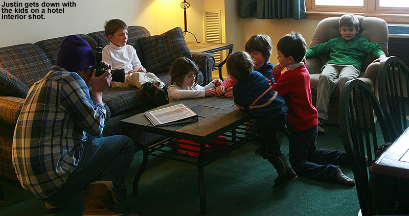 An image of a photographer working with children in a hotel room at Bolton Valley Ski Resort in Vermont as he takes lifestyle photos