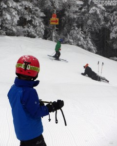 An image of Dylan watching photographer Justin Cash as he takes pictures of a skier on the Cobrass trail at Bolton Valley Resort in Vermont