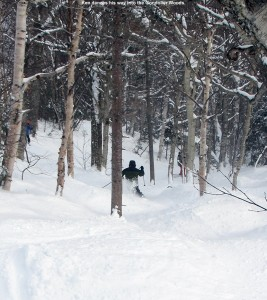 An image of Ken on skis dropping into the Gondolier Woods at Stowe Mountain Ski Resort in Vermont