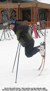 An image of Ken doing a tip stand on his skis outside the Spruce Camp Lodge at Stowe Mountain Resort in Vermont