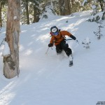 An image of Ty Telemark skiing in powder of the back side of  Bolton Valley Resort